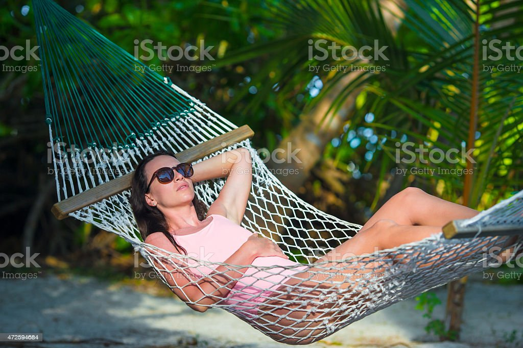 Woman in swimsuit relaxing on hammock sunbathing on vacation - Royalty-free 2015 Stock Photo