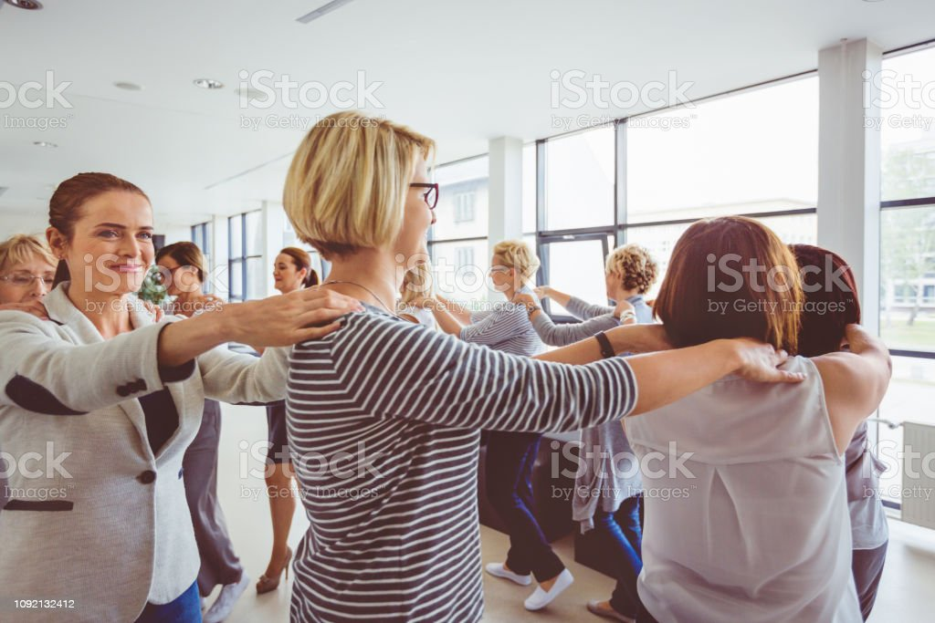 Woman in team building workshop Group of business women walking in circle as a routine of a training workshop in office. Team building training programme for businesswomen. Adult Stock Photo