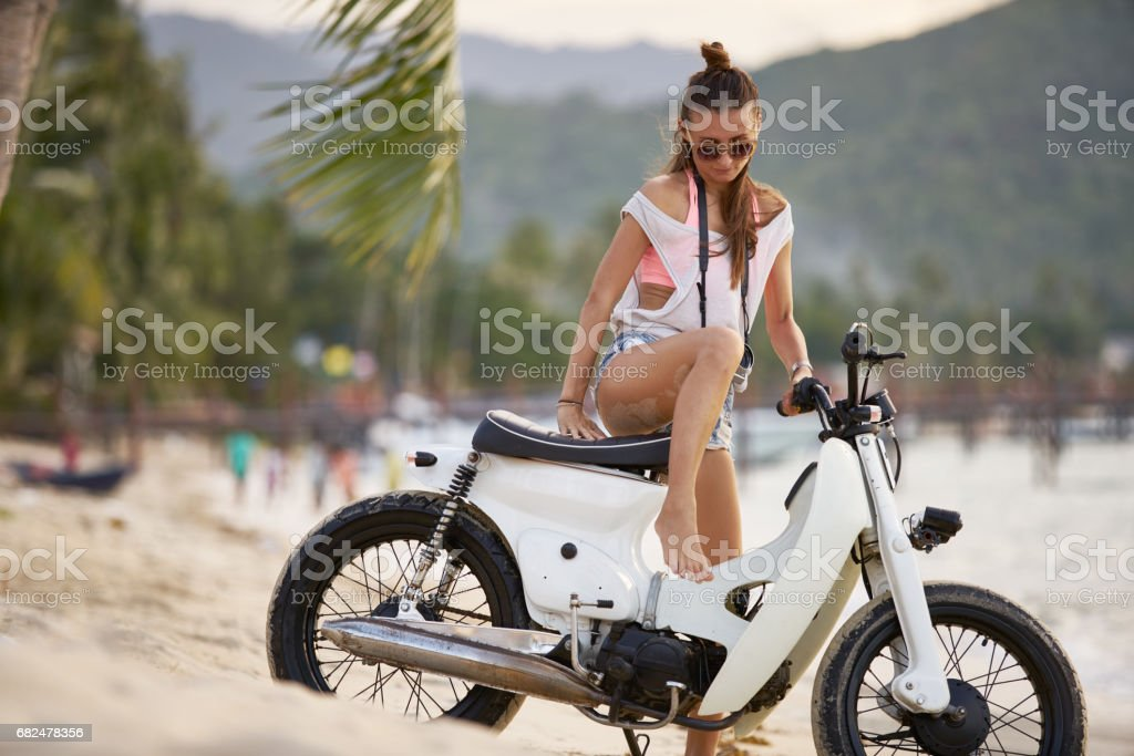 woman in thailand getting on motorbike royalty-free stock photo
