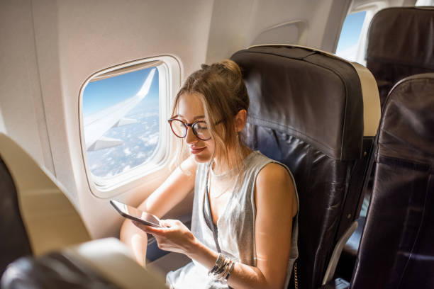 Woman in the airplane Young woman sitting with phone on the aircraft seat near the window during the flight in the airplane passenger stock pictures, royalty-free photos & images