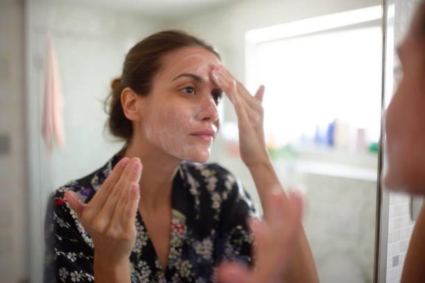 femme dans la salle de bains - démaquillant photos et images de collection