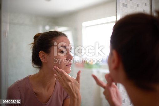 Young female in the bathroom looking in the mirror and taking care of her facial skin.