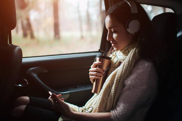kvinna i bilen, höst koncept. leende söt flicka lyssnar på musik med hörlurar och läsa en bok som rör sig i bilen. - happy indie pop bildbanksfoton och bilder