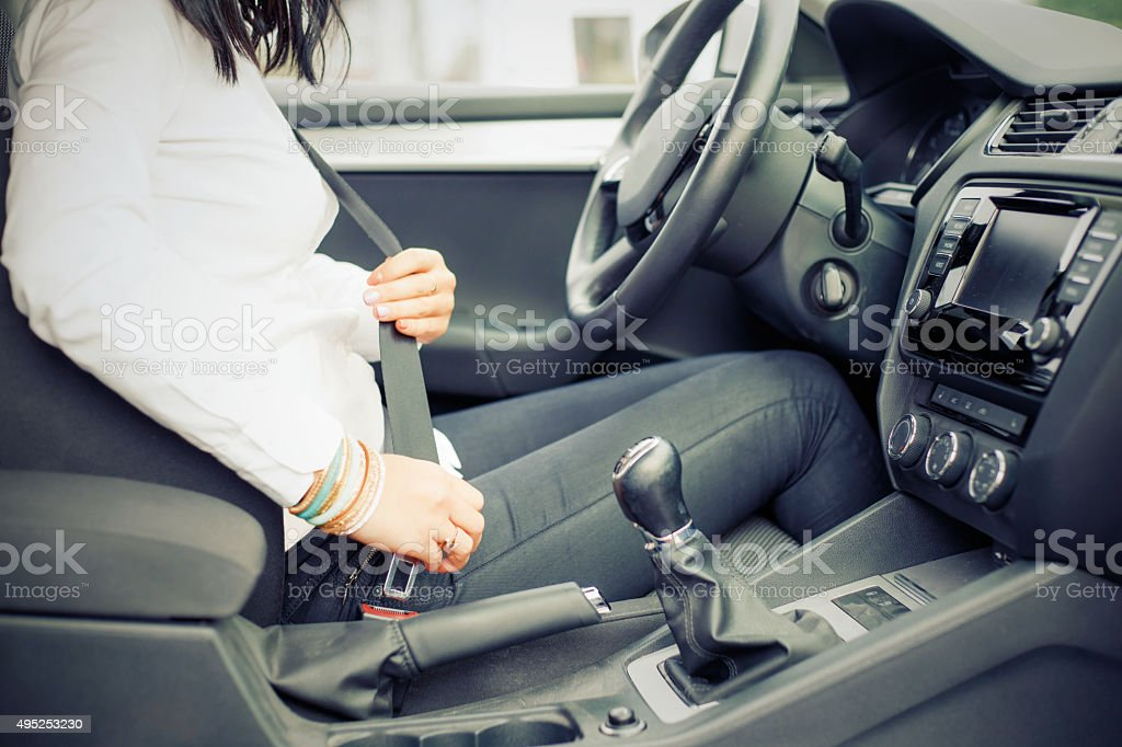 Woman in the car buckling up stock photo
