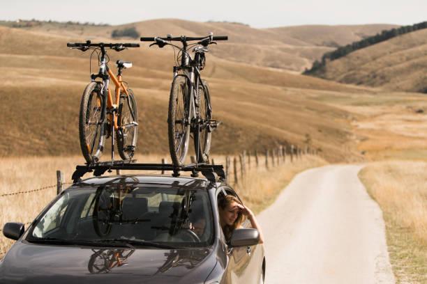 frau im auto mit dem fahrrad auf dem dach befestigt - fahrradträger stock-fotos und bilder