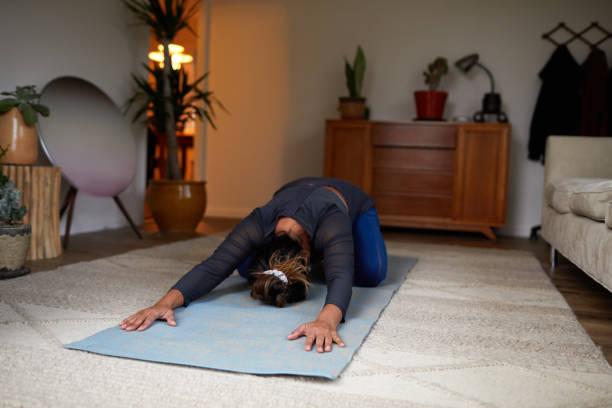 Frau in der Pose des Kindes beim Yoga zu Hause – Foto
