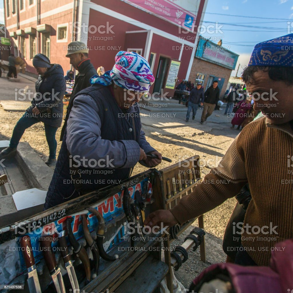 Woman in the city market sells daggers. stock photo
