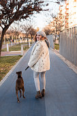Woman in the city walking with her dog in full length portrait and looking smile at camera.