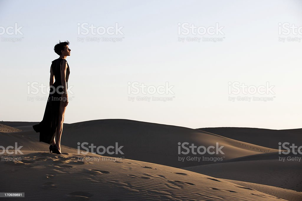 Young beautiful woman looking over the desert dunes at dusk