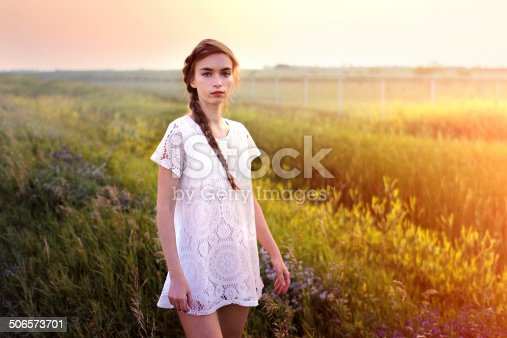 A portrait of a young woman in a white dress standing in the summer field. Shot in Winnipeg, Manitoba, Canada.
