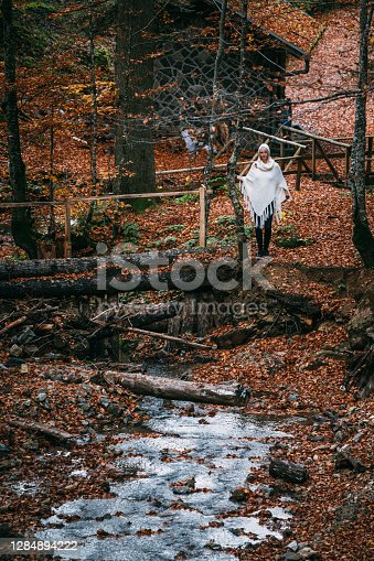 A woman in a white poncho stands by a wooden bridge over a small stream in a forest covered with autumn leaves fallen from a trees