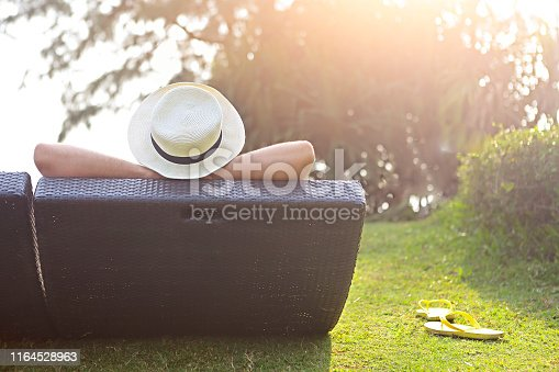Relaxed woman in the hat sitting at the beach at sunset time