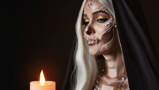 istock A woman in the image of an attractive mysterious witch with white ashy hair holds a burning candle. Creative makeup for Halloween party. Black poppy and dark backdrop. Celebrating Dia de los Muertos 1184029016