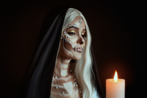 istock A woman in the image of an attractive mysterious witch with white ashy hair holds a burning candle. Creative makeup for Halloween party. Black poppy and dark backdrop. Celebrating Dia de los Muertos 1184030077