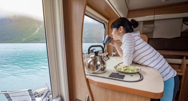 Frau im Inneren eines Wohnmobil Wohnmobilmitstroms mit einer Tasse Kaffee mit Blick auf die Natur. – Foto