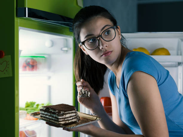 woman in the kitchen having a late night snack, she is taking a delicious dessert from the fridge, diet fail concept - donna si nasconde foto e immagini stock