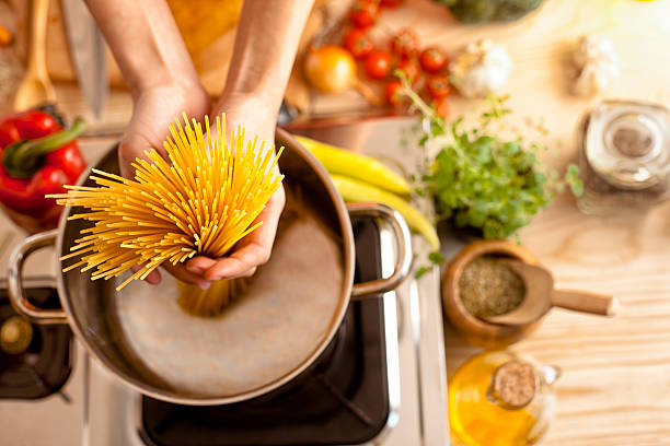 woman in the kitchen holding spaghetti stock photo