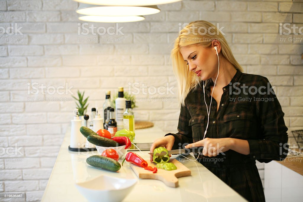 Woman in the kitchen listening music. stock photo