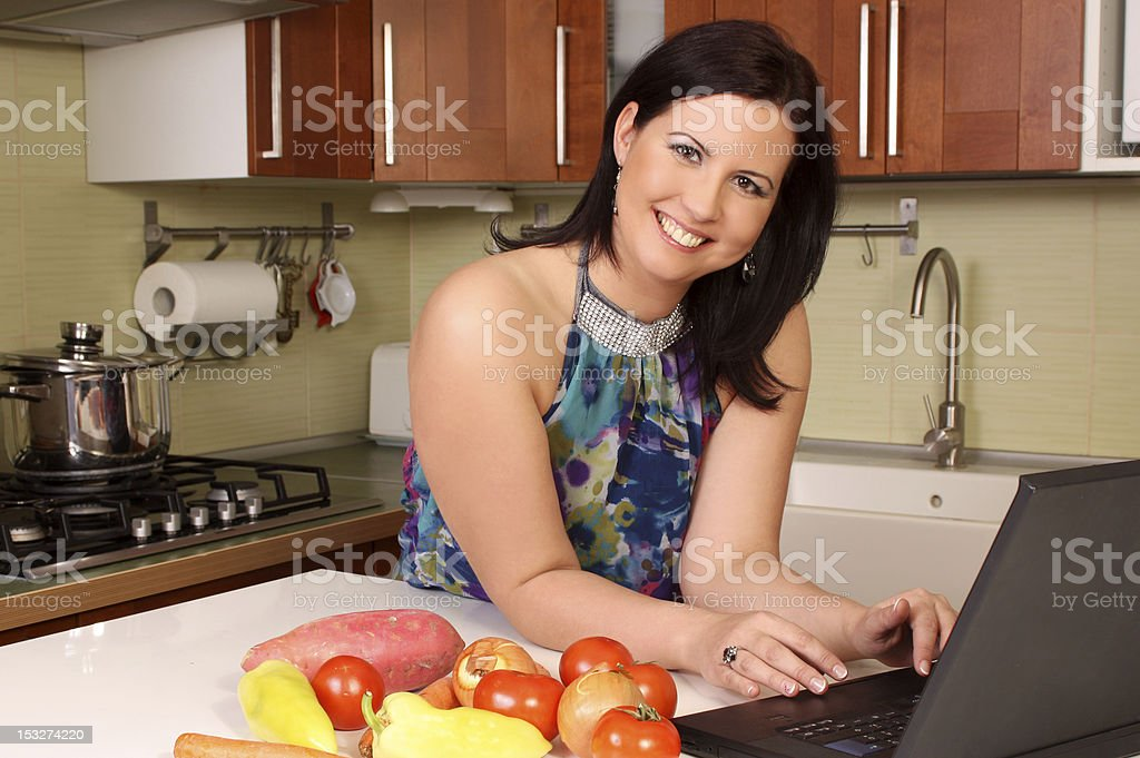 Woman in the kitchen looking for recipe royalty-free stock photo