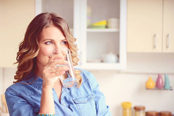 woman in the kitchen - drinking water stock photos and pictures