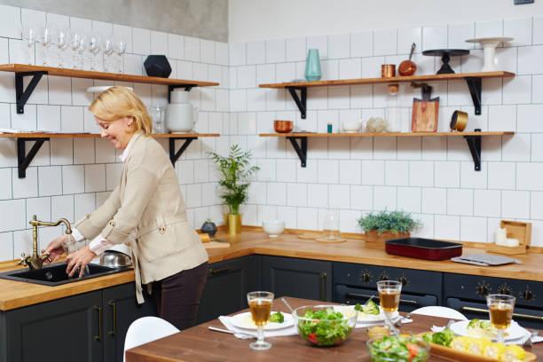 frau in der küche - glaswaschtisch stock-fotos und bilder