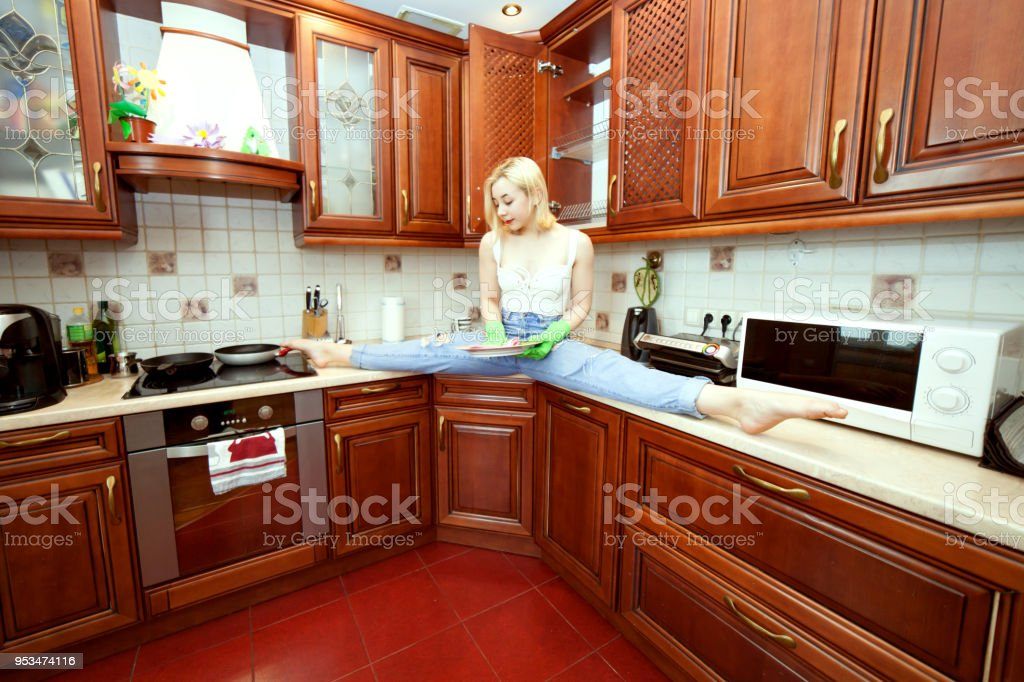Woman in the kitchen washes the plates. stock photo