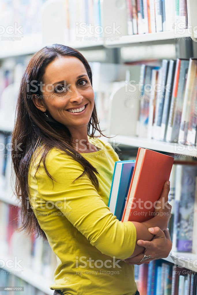 Woman in the library standing by the bookshelves stock photo