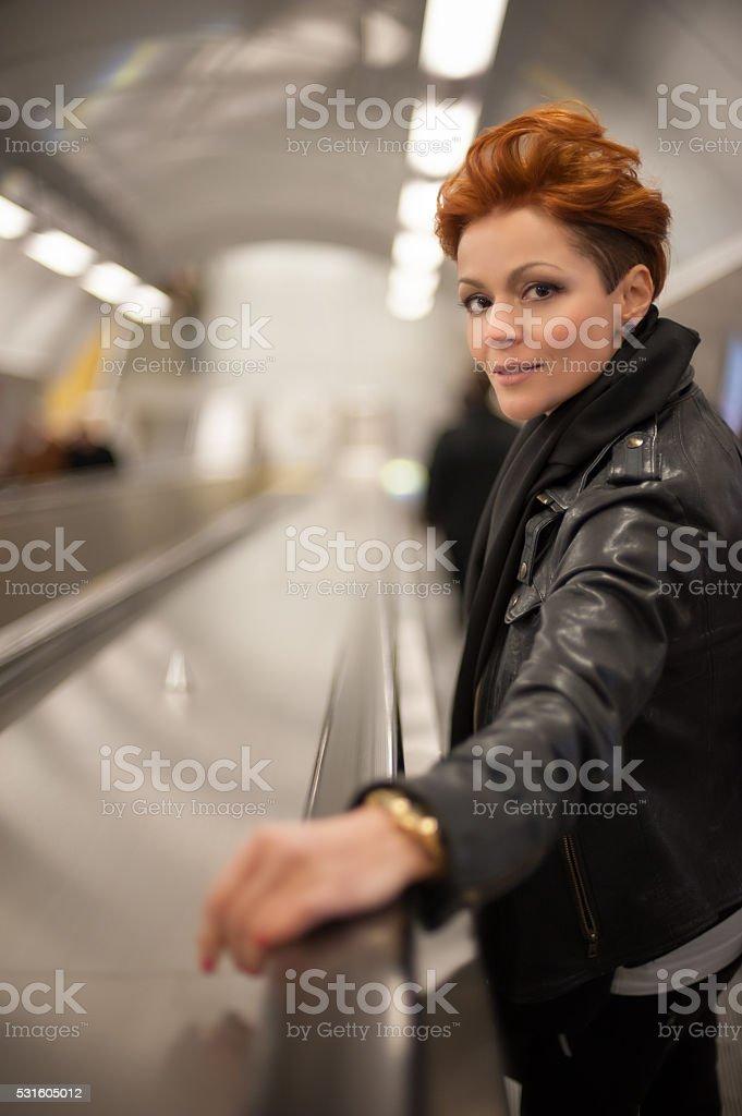 Woman in the metro escalator tounel stock photo