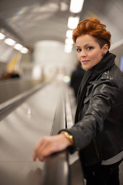 Woman in the metro escalator tounel stock photo