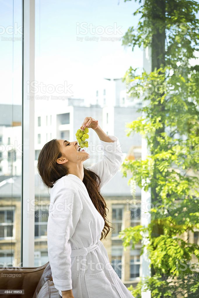 Woman in the morning Beautiful young woman wearing white bathrobe standing in her apartment and eating green grapes. 20-24 Years Stock Photo