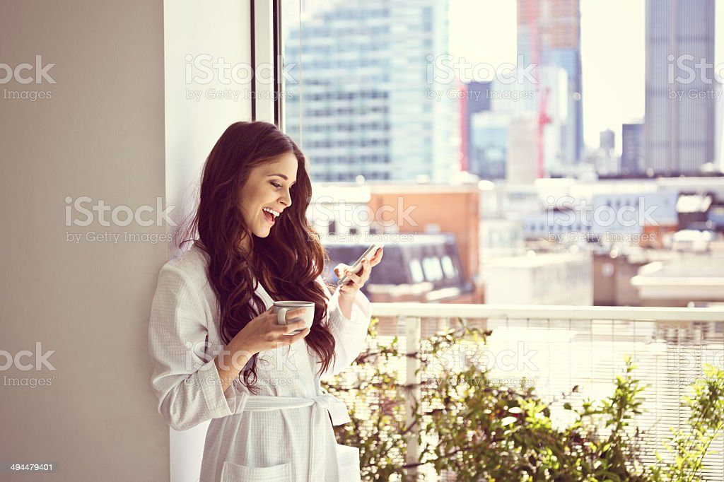 Woman in the morning Beautiful young woman wearing white bathrobe standing with cup of coffee in her apartment in the morning and using a smart phone. 20-24 Years Stock Photo