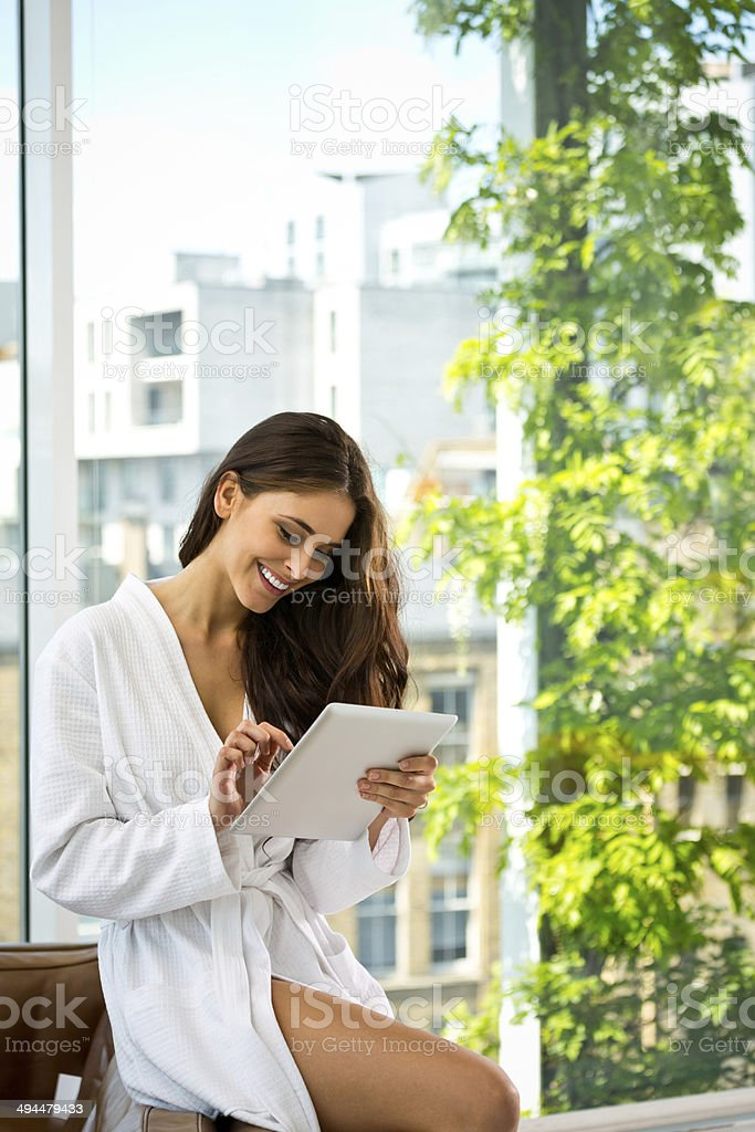 Woman in the morning Beautiful young woman wearing white bathrobe standing in her apartment and using a digital tablet. 20-24 Years Stock Photo