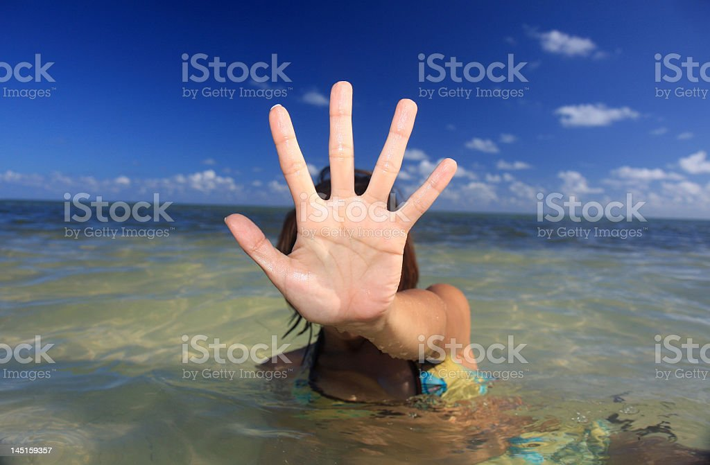 Woman in the ocean with hand in front of the camera  royalty-free stock photo
