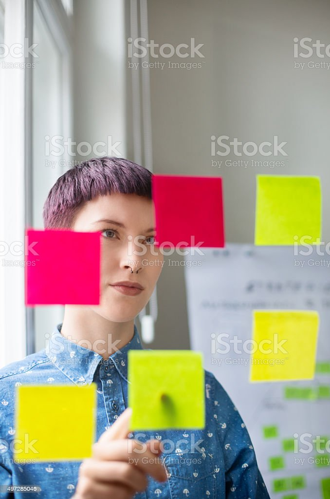 Woman in the office looking at posit notes stock photo