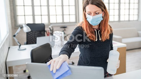 Woman in the office using disinfectant  for sanitizing monitor surface during COVID-19 pandemic