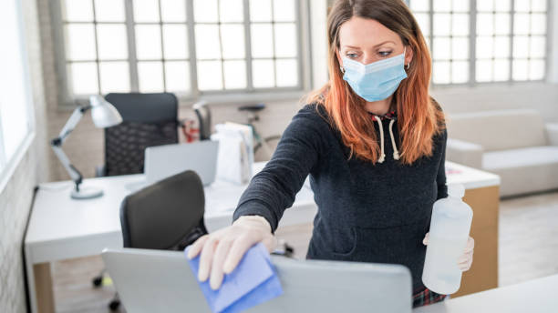 Woman in the office using disinfectant  for sanitizing monitor surface during COVID-19 pandemic Woman in the office using disinfectant  for sanitizing monitor surface during COVID-19 pandemic protective workwear stock pictures, royalty-free photos & images