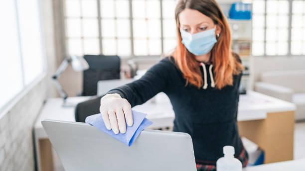 Frau im Büro mit Desinfektionsmittel zur Desinfektion der Monitoroberfläche während der COVID-19-Pandemie – Foto