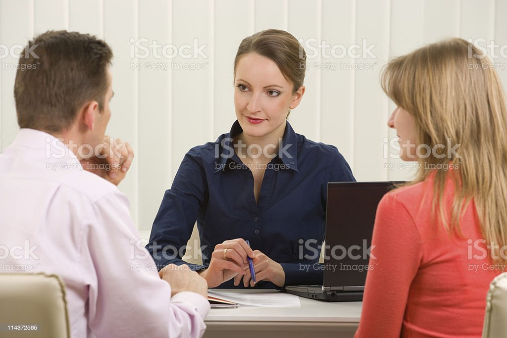 A woman in the office with potential clients, man and woman  stock photo
