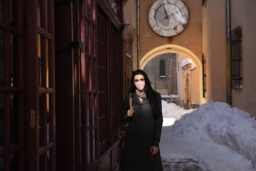 Woman in the old European city. Quarantine time.