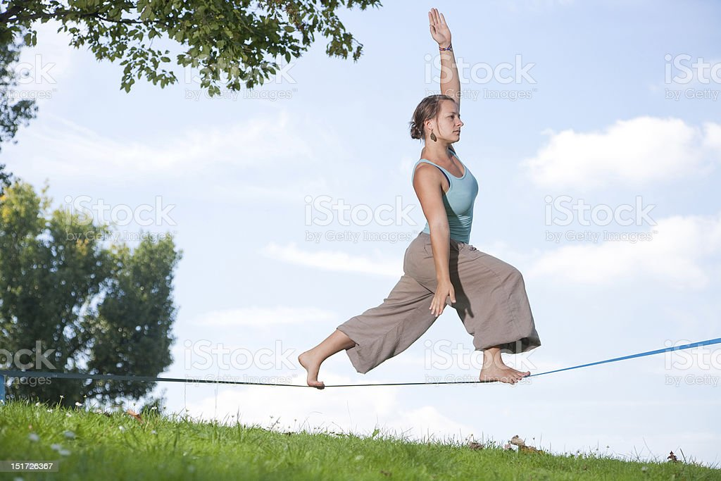 A woman in the park walking on a tight rope stock photo