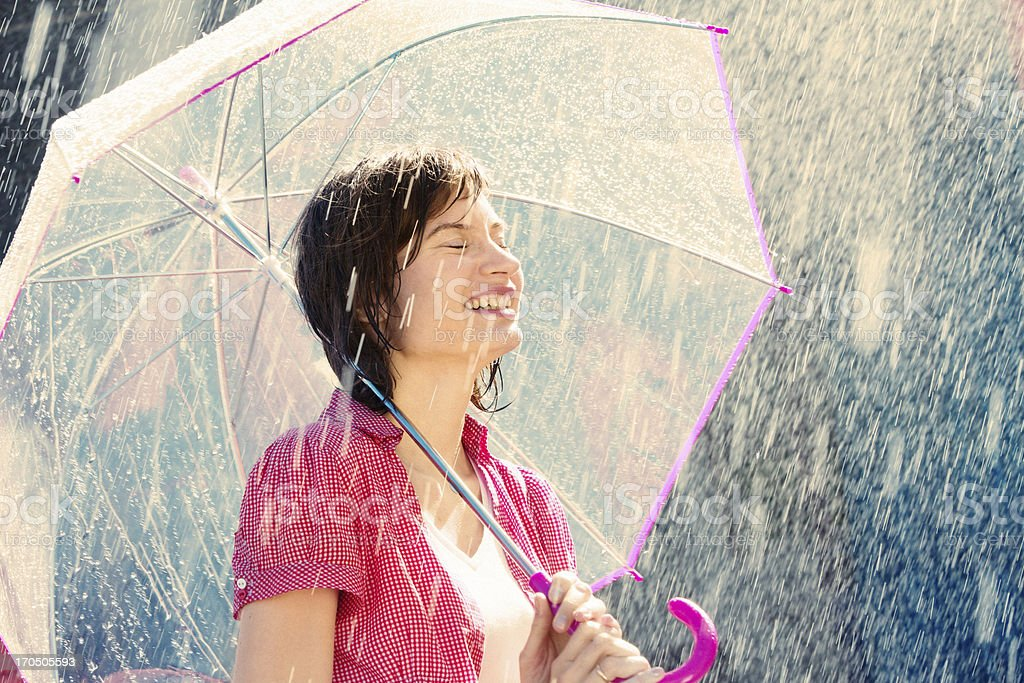 Woman in the rain with a pink and clear umbrella royalty-free stock photo