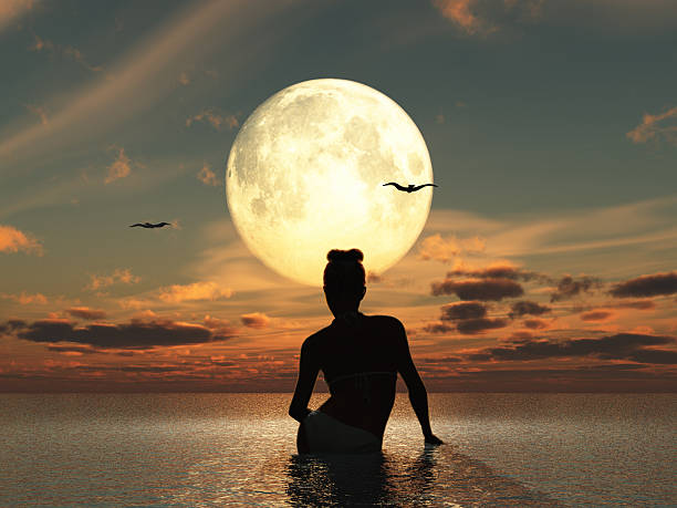 Woman in the sea watching the full moon stock photo