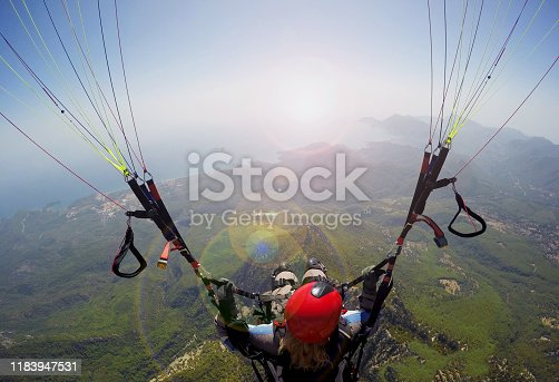 istock Woman in the sky paragliding 1183947531