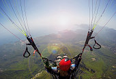 Paragliding in the sky. Woman girl is soaring in the sky on paraplane above mountains ans sea