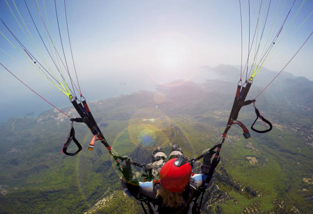 Woman in the sky paragliding Paragliding in the sky. Woman girl is soaring in the sky on paraplane above mountains ans sea paragliding stock pictures, royalty-free photos & images
