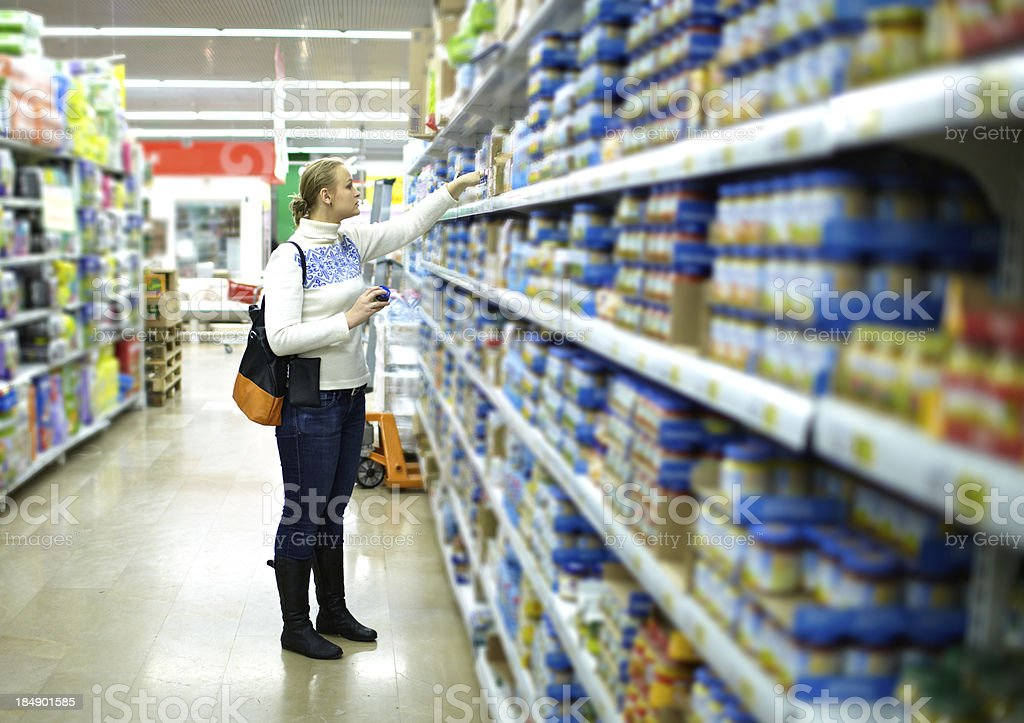 Woman in the supermarket. Kid's food. stock photo
