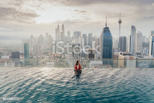 Young Caucasian woman in the swimming pool with view of Kuala Lumpur