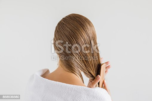 istock Woman in the white towel with comb brushing her wet blonde hair after shower on the gray background. Cares about a healthy and clean hair. Beauty salon concept. 858536580