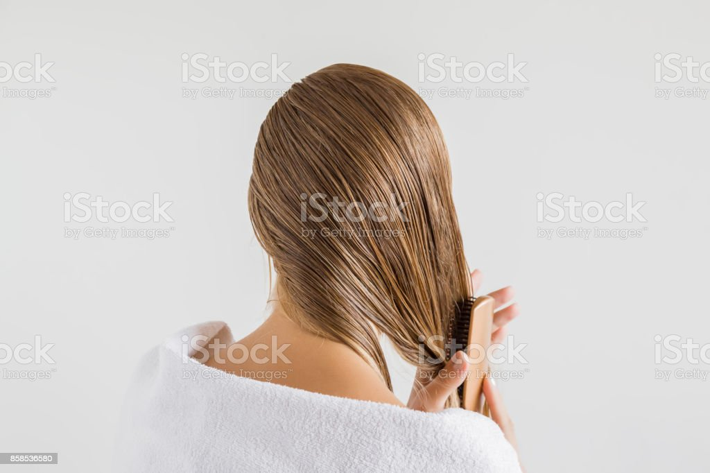 Woman in the white towel with comb brushing her wet blonde hair after shower on the gray background. Cares about a healthy and clean hair. Beauty salon concept. stock photo