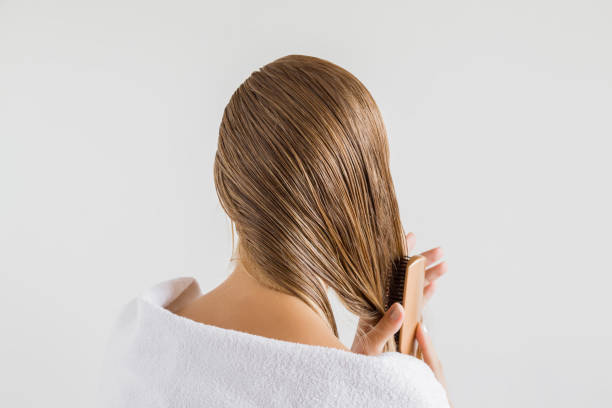 woman in the white towel with comb brushing her wet blonde hair after shower on the gray background. cares about a healthy and clean hair. beauty salon concept. - human hair stock photos and pictures